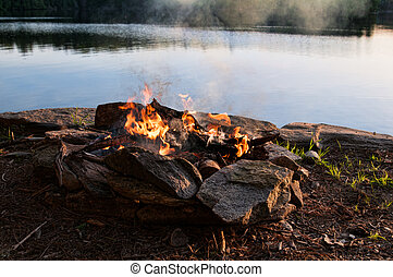 camp fire - bonfire overlooking a lake