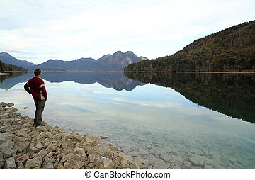 hiker is looking to lake with mountains
