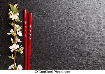 Japanese sushi chopsticks and sakura blossom on black stone...
