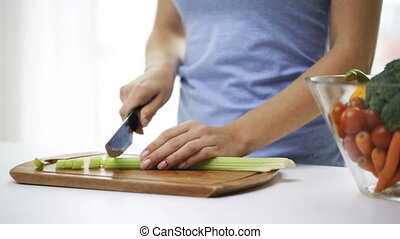 close up of young woman chopping celery at home - healthy...