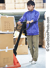 chinese warehouse worker with forklift stacker