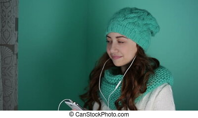 Beautiful girl in a knitted hat listening to music on...