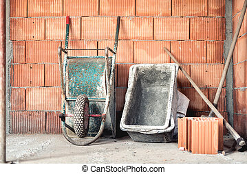 Brick layering with mortar, wheel barrow and cement mixer on...