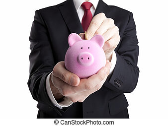 Putting coin into the piggy bank - Businessman putting coin...