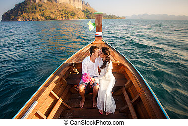 bride and groom kiss in longtail boat - brunette bride in...