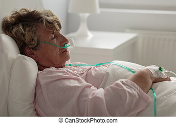 Sick woman with nasal cannula - Image of sick woman with...