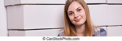 Smiling girl and cardboard boxes in background
