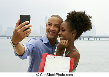 African American Couple Shopping Taking Selfie With Mobile...