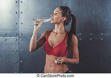 Muscular sporty athlete woman drinking water at the gym...