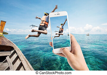 Taking photo of snorkeling divers jump in the water. -...