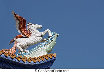 pegasus sculpture on rooftop with blue sky background
