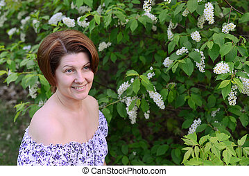 adult woman near blossoming bird cherry in the park - An...