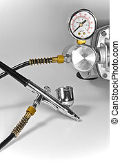 Metal shiny air brush with pressure gauge and pipes.