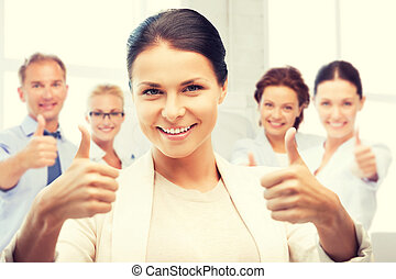 businesswoman showing thumbs up in office - business and...