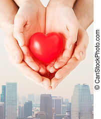 close up of couple hands holding red heart - health, love...