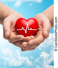 close up of hands holding heart with cardiogram - family...