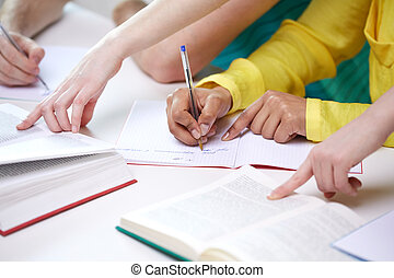 close up of students hands writing to notebooks - education,...