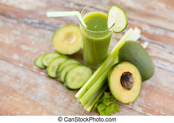 close up of fresh green juice glass and vegetables - healthy...