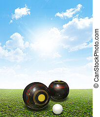 Bowls On Lawn - A set of wooden lawn bowls next to a jack on...