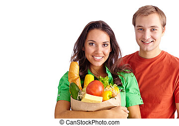 Healthy couple - Happy girl holding sack with products and...