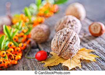 autumn background - hawthorn and walnuts on the wooden table