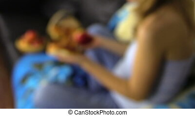 hand hold apple and bun - change of focus pregnant woman...