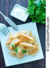 fried dumplings on the white plate and on a table