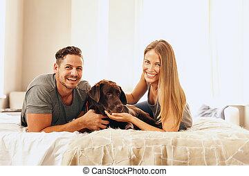 coppia, giovane, letto, cane, loro, dire bugie
