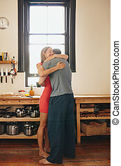 Young couple embracing each other in kitchen
