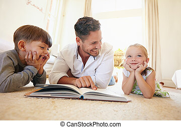 Father with two kids reading a story book. - Portrait of...