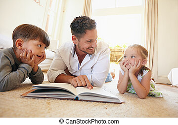 Young man with two kids reading a story book - Indoor shot...