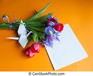 bouquet on the table - tulips and irises lie on a orange...