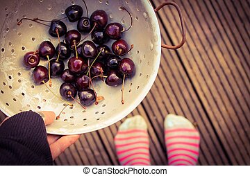 Home grown cherries - personal perspective hand holding a...