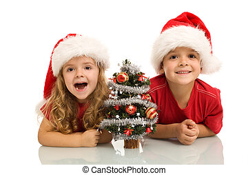 Kids with small decorated tree at christmas time - Surprised...