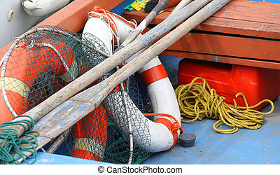 lifebuoys fishing nets and oars in a boat moored