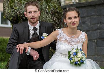 Newlyweds before stone wall - junge Brautleute vor einem...