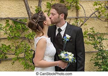 Newlyweds kissing - junges kuessendes Brautpaar vor einem...