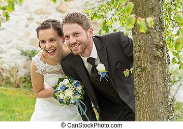 happy bride and groom under a tree - gluecklich lachende...