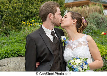 Kiss a married couple - junges kuessendes Hochzeitspaar im...
