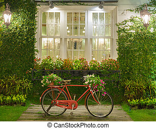 red bicycle with white window and garden background - old...