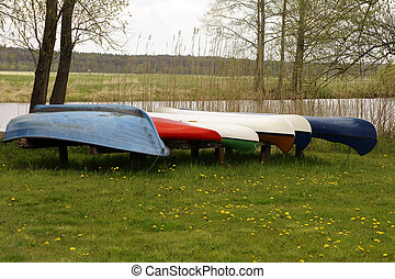 Canoes jacked riverside - A number of canoes and rowboats...