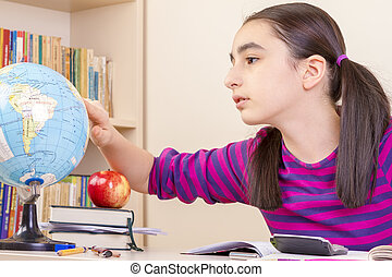 Schoolgirl learns geography - Cute little girl doing...