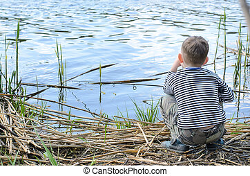 Serious Boy Sitting on Riverside While Fishing - Rear View...