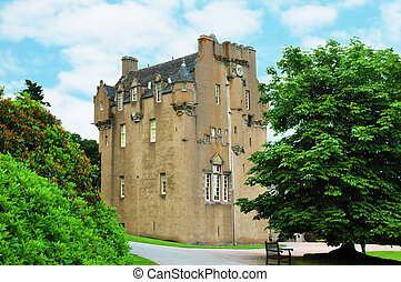 Scottish castle between the trees in summer day