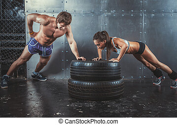 Sportswomen Fit sporty woman and man doing push ups on tire...