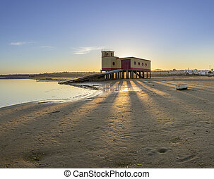 Sunset and historic life-guard building in the foreground, at Fuseta fishing town, Ria Formosa conservation park, Algarve.