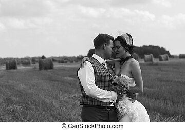 Bride and groom near hay on a rural field - Bride and groom...