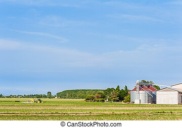 Agricultural landscape with farm,silos and tractor