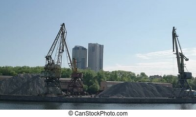 Old port cranes moving on the riverside against new buildings