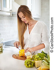Young smiling woman cooking vegetables at the kitchen